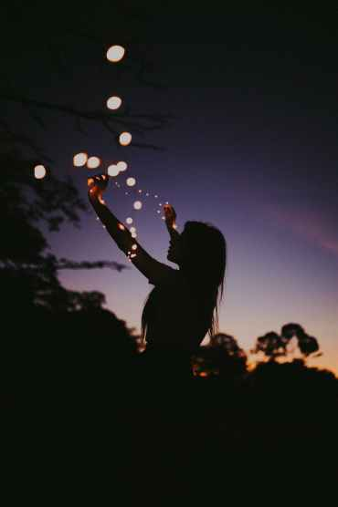 silhouette photo of woman holding lights